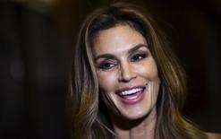 "U.S. model Cindy Crawford reacts as she takes part in an interview at the launch party of her autobiographical book ""Becoming"" in central London, Britain, October 1, 2015. REUTERS/Toby Melville"