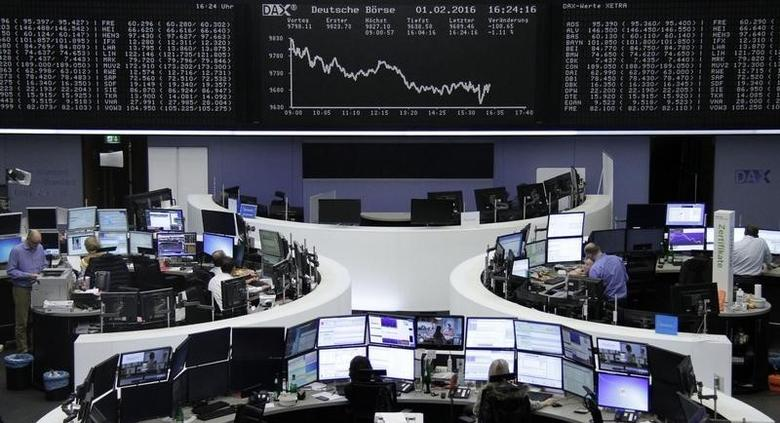 Traders work at their desks in front of the German share price index, DAX board, at the stock exchange in Frankfurt, Germany, February 1, 2016.     REUTERS/Staff/Remote
