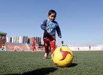 Five year-old Murtaza Ahmadi, wears Barcelona's star Lionel Messi shirt made of a plastic bag , as he plays football at the Afghan Football Federation headquarter in Kabul, Afghanistan February 2, 2016.  REUTERS/Omar Sobhani