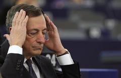 Los intereses de la deuda de la zona euro caían ante el abaratamiento del petróleo y la reiteración por parte del presidente del Banco Central Europeo (BCE) de que revisará la política monetaria del bloque el próximo mes. En esta imagen de archivo, el presidente del Banco Central Europeo, Mario Draghi, ajusta sus auriculares antes de un debate en el Parlamento Europeo en Estrasburgo, el 1 de febrero de 2015. REUTERS/Vincent Kessler