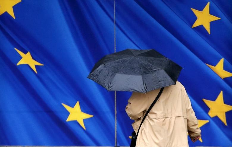 A woman carrying an umbrella walks towards the European Commission headquarters in Brussels, Belgium February 2, 2016.   REUTERS/Francois Lenoir