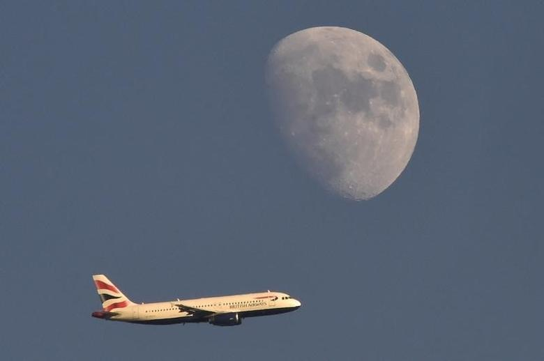 A British Airways passenger plane flies in the sky with the moon seen in the background, in London, Britain, January 19, 2016. REUTERS/Toby Melville