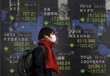 Un peatón camina junto a un tablero electrónico que muestra la información de los índices de mercado de varios países, afuera de una correduría en Tokio, Japón, 3 de febrero de 2016. Las bolsas de Asia caían el miércoles en momentos en que los precios del petróleo se desplomaban por tercer día consecutivo, lo que llevaba a los inversores a buscar refugio en activos vistos como seguros e impulsaba a los precios de los bonos y el oro a máximos en varios meses. REUTERS/Yuya Shino
