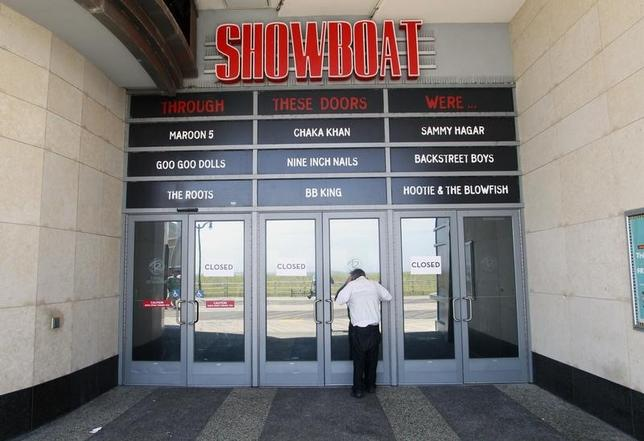 A man tries to peek into the closed Showboat Casino Hotel in Atlantic City, New Jersey in this September 1, 2014 file photo.  REUTERS/Tom Mihalek