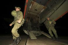 """Российские морпехи, охранявшие авиабазу Хмеймим в Сирии, выходят из самолета по прилету в аэропорту Бельбек в крымском Севастополе 28 декабря 2015 года. Кремль опроверг в четверг, что погибший в Сирии от артобстрела """"террористами ИГИЛ"""" российский военный участвовал в каких-либо наземных операциях в конфликте, в котором Москва помогает силам Башара Асада ударами с воздуха. REUTERS/Pavel Rebrov"""