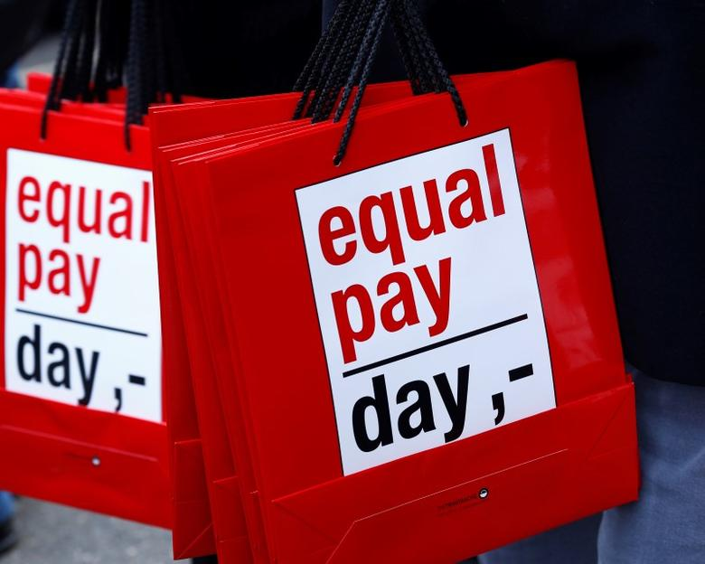 People carry bags reading 'equal pay day' during a protest a day before International Women's Day, in Bern March 7, 2015.  REUTERS/Ruben Sprich