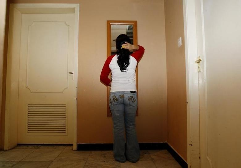 Fatima from Uzbekistan, a resident of the City of Hope shelter for women, looks in the mirror in Dubai February 14, 2008.   REUTERS/Ahmed Jadallah
