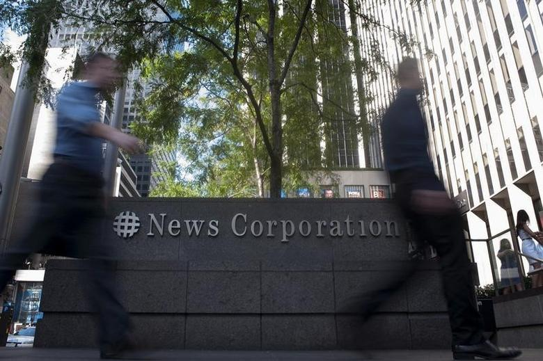 Passers-by walk near the News Corporation building in New York in this June 28, 2012 file photo. REUTERS/Keith Bedford