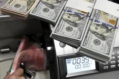 Сотрудник подразделения  Bank of China считает юани и доллары.  Доллар стабилизировался в ходе азиатских торгов в пятницу, но продолжает двигаться к недельным потерям, пока инвесторы ждут публикации данных о занятости в США, чтобы спрогнозировать дальнейшие действия ФРС в отношении повышения ключевой ставки. REUTERS/Jon Woo