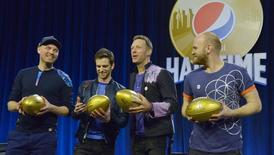 Feb 4, 2016; San Francisco, CA, USA; Recording artists from left Jonny Buckland , Guy Berryman , Chris Martin and Will Champion of Coldplay are presented with gold souvenir footballs during the Super Bowl 50 halftime show press conference at Moscone Center. Mandatory Credit: Kirby Lee-USA TODAY Sports