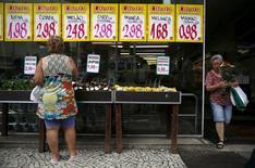 Mulher observa placas com preços de alimentos em mercado no Rio de Janeiro. 21 de janeiro de 2016.REUTERS/Pilar Olivares
