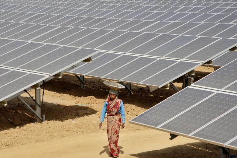 A worker walks through the installed solar modules at the Naini solar power plant in Allahabad March 21, 2012. REUTERS/Jitendra Prakash/Files