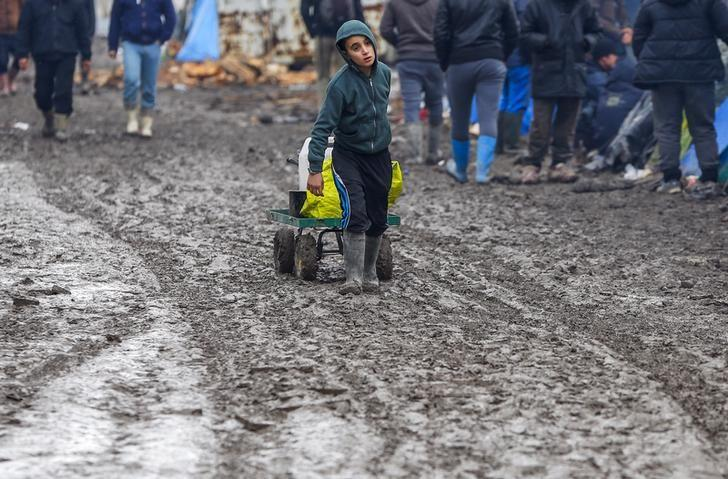 A young migrant pulls a trolley in a muddy field at a camp of makeshift shelters for migrants and asylum-seekers from Iraq, Kurdistan, Iran and Syria, called the Grande Synthe jungle, near Calais, France, February 3, 2016.  REUTERS/Yves Herman