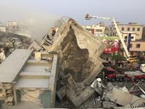 Спасатели ищут выживших после обрушения жилого дома в Тайнане. 6 февраля 2016 года. Жертвами мощного землетрясения, произошедшего ранним утром в субботу на Тайване, стали как минимум 12 человек, большинство из них погибли в результате обрушения многоэтажного жилого дома, сообщили власти. REUTERS/Pichi Chuang