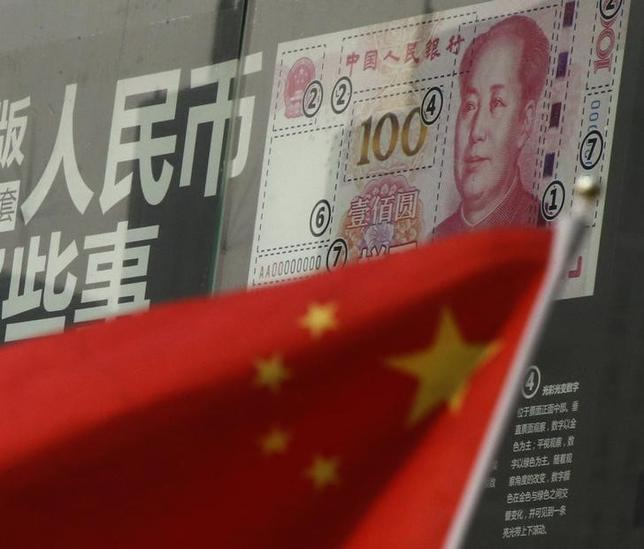 China's national flag is seen in front of a poster explaining the design of new 100 yuan banknote at a branch of a commercial bank at a business district in Beijing, China, January 21, 2016. REUTERS/Kim Kyung-Hoon