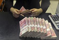 Служащий China Merchants Bank пересчитывает банкноты в 100 юаней. Валютные резервы Китая снизились третий месяц подряд в январе, поскольку центробанк страны сбрасывал доллары для защиты юаня и предотвращения большего оттока капитала. REUTERS/Stringer