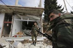 солдаты, лояльные президенту Сирии Башару Асаду стоят напротив разрушенного магазина в городе Ар-Рабия. Сирийская армия продвинулась в сторону границы с Турцией в ходе крупного наступления в понедельник, поддерживаемого Россией и Ираном, которое, как опасаются повстанцы, уже угрожает будущему их почти пятилетнего восстания против президента Башара Асада. REUTERS/Omar Sanadiki