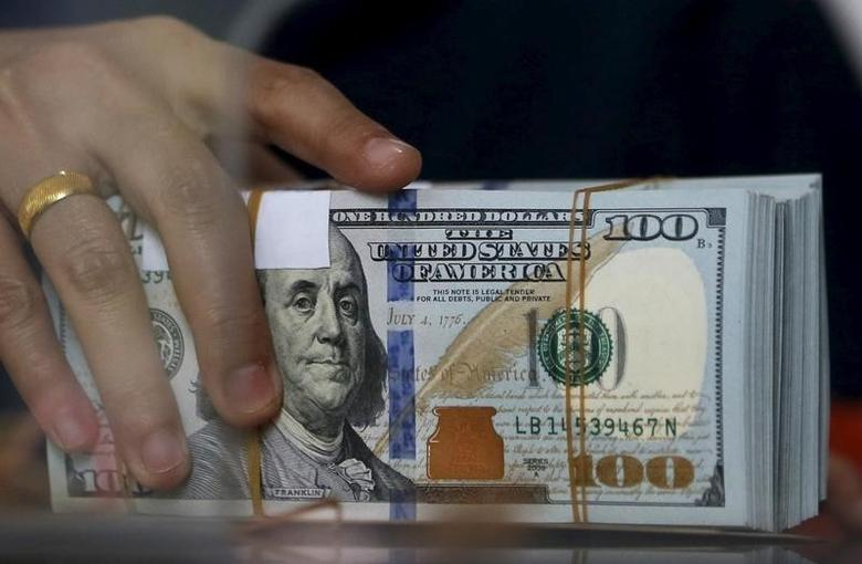 An employee of a money changer holds a stack of U.S.  Dollar notes before giving it to a customer in Jakarta, October 8, 2015. REUTERS/Beawiharta