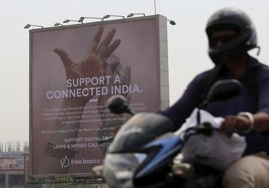 A motorist rides past a billboard displaying Facebook's Free Basics...
