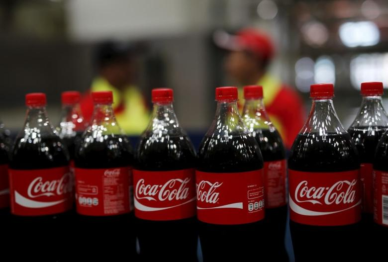 Workers stand near bottles of Coca-Cola on a newly inaugurated production line at the Cikedokan Plant in Bekasi, West Java near Jakarta March 31, 2015.  REUTERS/Darren Whiteside