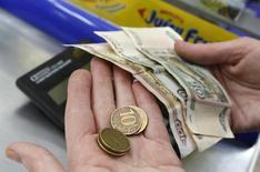 Продавец в магазине Красноярска пересчитывает рублевые банкноты и монеты. Рубль днем вторника пытается закрепиться в плюсе за счет роста нефтяных котировок и снижения градуса напряженности на мировых рынках после распродаж, спровоцированных накануне опасениями в отношении мировой экономики.REUTERS/Ilya Naymushin