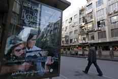 """Человек проходит мимо рекламного щита, призывающего сирийцев вступать в вооруженные силы. Дамаск, 12 ноября 2015 года.  Несколько человек погибли, когда смертник взорвал начинённый взрывчаткой автомобиль у здания клуба полицейских в жилом районе Дамаска, сообщило МВД Сирии об атаке, ответственность за которую взяло """"Исламское государство"""". REUTERS/Omar Sanadiki"""