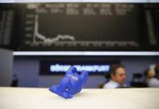 A styrofoam bull figure lies on its side on a counter in front of the German share price index DAX board at Frankfurt's stock exchange in Frankfurt, Germany January 7, 2016. REUTERS/Kai Pfaffenbach