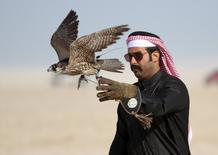 A Qatari man releases his falcon during a falcon contest at Qatar International Falcons and Hunting Festival at Sealine desert, Qatar January 29, 2016. REUTERS/Naseem Zeitoon