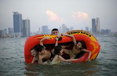 A man plays with his family at Mamzar beach in Dubai, United Arab Emirates in this October 25, 2013 file photo. REUTERS/Ahmed Jadallah/Files