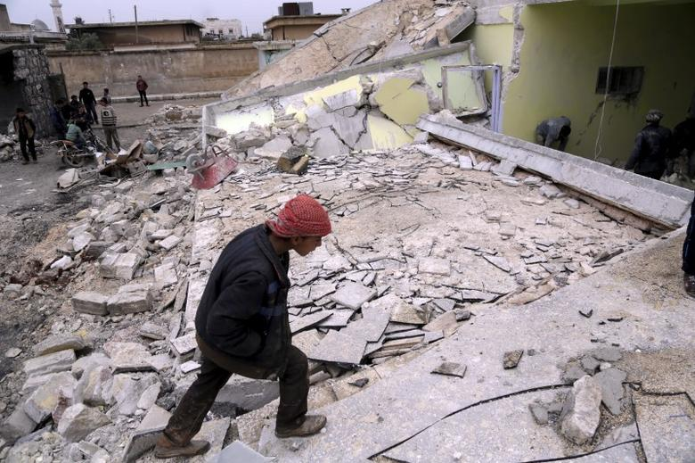 A boy inspects his school, damaged in what activists said was an air strike carried out yesterday by the Russian air force in Injara town, Aleppo countryside, Syria January 12, 2016.   REUTERS/Khalil Ashawi