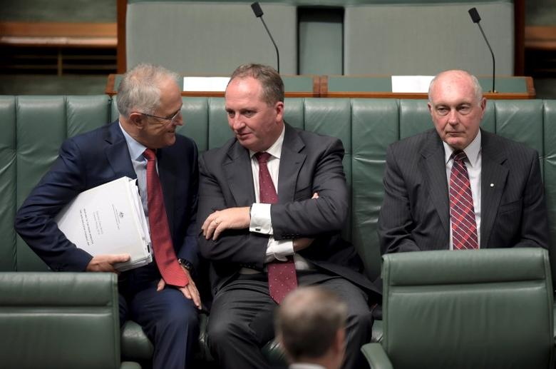 Australian Prime Minister Malcolm Turnbull (L) speaks to Australian Agriculture Minister Barnaby Joyce (C) as Federal Minister for Infrastructure and Regional Development Warren Truss sits next to them in the House of Representatives at Parliament House in Canberra, Australia, February 11, 2016. REUTERS/Lukas Coch/AAP