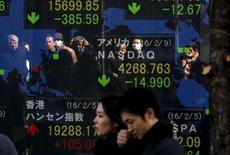 Personas se reflejan en una pantalla que muestra los índices de varios mercados, afuera de una correduría en Tokio, Japón,  10 de febrero de 2016. Nuevas grietas aparecieron el jueves en los mercados de Asia cuando los inversores buscaron la seguridad del yen, el oro y los bonos de primera categoría y se deshicieron del dólar por las apuestas de que la Reserva Federal de Estados Unidos podría aplazar las alzas de las tasas de interés en ese país. REUTERS/Thomas Peter