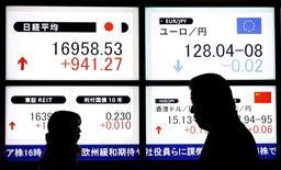 Пешеходы идут мимо табло, демонстрирующего показатели индекса Nikkei и курс иены к евро. Иена подскочила на 2 процента к доллару, достигнув максимума 15 месяцев в четверг, так как очередная волна притока капитала в традиционно безопасную японскую валюту повысила ожидания официального вмешательства для ослабления ее роста. REUTERS/Toru Hanai