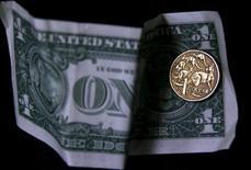 Монета в один австралийский доллар лежит на долларовой купюре США. Доллар ослаб в пятницу и может понести существенные недельные потери против основных валют, так как многие инвесторы отдают предпочтение безопасной иене в условиях снижения мировых рынков.  REUTERS/David Gray/Illustration