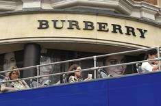 Visitors on an open-top tour bus drive past a Burberry store in central London, Britain July 15, 2015. REUTERS/Toby Melville