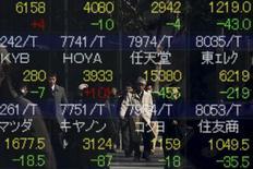 Personas se reflejan en una pantalla que muestra los índices de mercado de varios países, afuera de una correduría en Tokio, Japón, 10 de febrero de 2016. Las bolsas de Asia caían por sexta sesión consecutiva el viernes, en momentos en que las preocupaciones sobre la salud de los bancos europeos amenazaban a una economía global ya presionada por la caída de los precios del crudo y la desaceleración en China y otros mercados emergentes. REUTERS/Thomas Peter