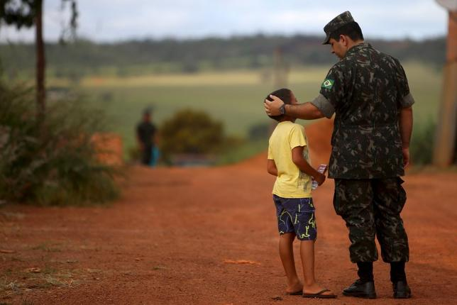 A Brazilian Army soldier talks with a child during the National Day of Mobilization Zika Zero at Sao Sebastiao neighbourhood in Brasilia, Brazil, February 13, 2016.  REUTERS/Adriano Machado