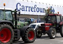 La minorista francesa Carrefour reveló el domingo que habían registrado oficinas suyas dentro de una investigación sobre sus prácticas comerciales, dos días después de que el gobierno advirtiera a las empresas contra los intentos por provocar nuevos recortes de precios de los agricultores. En esta imagen de archivo, unos tractores bloquean la entrada de un supermercado de Carrefour durante una protesta de productores lácteos belgas por los bajos precio de la leche, en Waterloo el  31 de julio de 2015.  REUTERS/Francois Lenoir