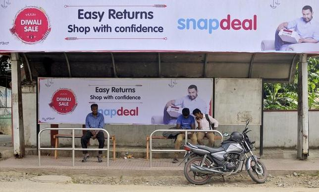 Commuters sit at a bus stop adorned with an advertisement of Indian online marketplace Snapdeal featuring Bollywood actor Aamir Khan, in Bengaluru, India, October 15, 2015. REUTERS/Abhishek Chinnappa/Files