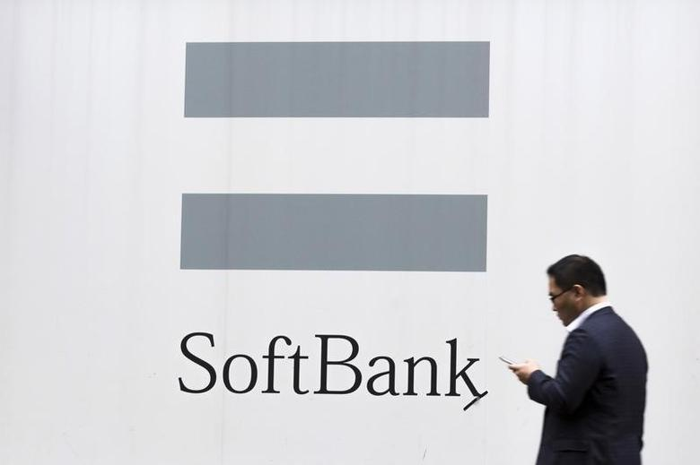 A man looks at his phone as he walks past an advertising poster of the SoftBank telecommunications company in Tokyo October 16, 2015. REUTERS/Thomas Peter