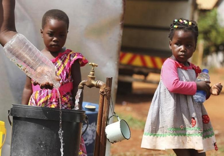 Zimbabwean children watch as their mother collects water from a communal tap in Harare, February 5, 2016. REUTERS/Philimon Bulawayo