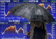 Un peatón con un paraguas pasea frente a una pantalla electrónica que muestra las fluctuaciones de índice japonés Nikkei en Tokio, el 18 de enero de 2016. Las acciones japonesas siguieron el ejemplo de unos repuntes en los mercados bursátiles de Europa y Wall Street y rebotaron con fuerza el lunes, haciendo caso omiso a unos datos que mostraron que la economía de Japón se contrajo más que lo esperado en el último trimestre del 2015. REUTERS/Yuya Shino