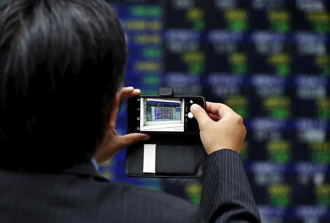 2月16日、東京株式市場で日経平均は続伸。序盤は前日の大幅高の反動売りで一時200円を超す下げとなったが、後場には一転、上げ幅が300円を超える場面があった。株価ボードを撮影する男性。都内で昨年6月撮影(2016年 ロイター/Issei Kato)