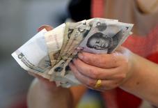 Los bancos chinos ofrecieron 2,51 billones de yuanes (385.400 millones de dólares) en préstamos nuevos en enero, un máximo histórico muy por encima de las expectativas, y el crecimiento de la masa monetaria se aceleró a un máximo en 19 meses, lo que sugiere que Pekín mantiene una política monetaria laxa para contrarrestar la desaceleración económica. En la imagen de archivo, un vendedor sostiene en sus manos billetes de yuan en un mercado en Pekín, el 12 de agosto de 2015. REUTERS/Jason Lee