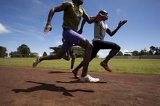 Athletes sprint during a training session on a dirt track in the town of Iten in western Kenya, November 13, 2015. Picture taken November 13, 2015. REUTERS/Siegfried Modola