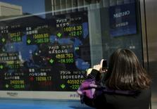 Una mujer toma fotografías de una pantalla que muestra los índices de mercado de varios países, afuera de una correduría en Tokio, Japón, 10 de febrero de 2016. Las bolsas de Asia caían el miércoles tras dos sesiones de ganancias sólidas, y los precios del petróleo avanzaban en momentos en que los inversores reconsideran las posibilidades de un acuerdo significativo para restringir la oferta de crudo más tarde en el año. REUTERS/Thomas Peter