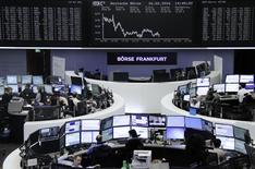 Traders work at their desks in front of the German share price index, DAX board, at the stock exchange in Frankfurt, Germany, February 16, 2016. REUTERS/Staff/remote