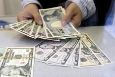 Una persona cuenta yenes japoneses para cambiarlos por dólares estadounidenses, en una casa de cambios en un distrito comercial en Tokio. 26 de noviembre de 2009. El yen frenó el miércoles su racha alcista, ya que los avances de los mercados bursátiles y de los precios del petróleo que afectaban el atractivo de la moneda japonesa, considerada como un activo de refugio. REUTERS/Kim Kyung-Hoon/Files