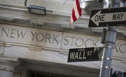 Las acciones subían el miércoles en la apertura de Wall Street y se encaminaban a su tercer día consecutivo de ganancias, en momentos en que los precios del petróleo continúan operando con alzas. En la imagen, la fachada de la Bolsa de Nueva York, junto a una señal  de tráfico, en Manhattan, el el 13 de agosto de 2015. REUTERS/Brendan McDermid