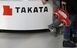 Visitors walk past a logo of Takata Corp on its display at a showroom for vehicles in Tokyo, Japan February 5, 2016. REUTERS/Toru Hanai